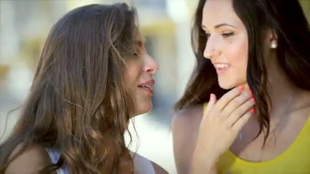 Two cute girls whisper while shopping