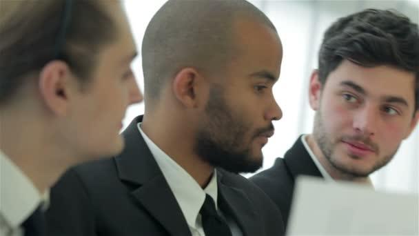 Három mosolygó sikeres üzletember ült az asztalnál hivatalban, miközben megbeszélte