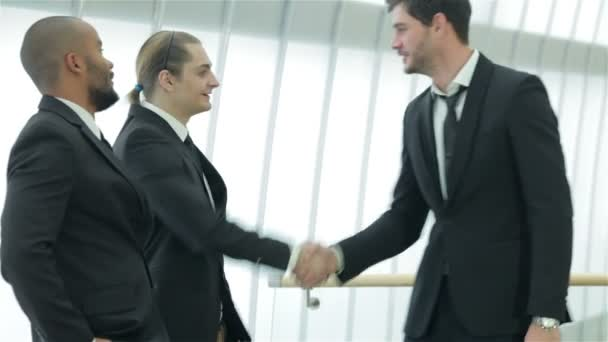 Two successful smiling businessmen shaking hands with each other