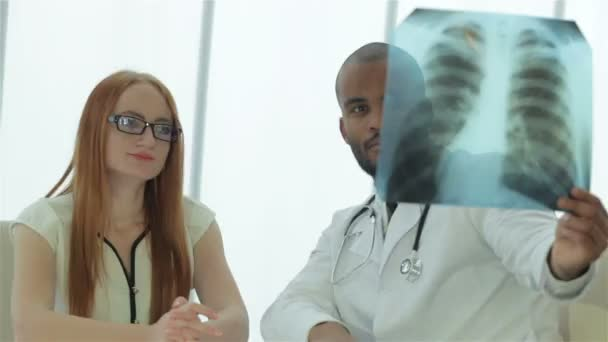 Serious Doctor talking to patient and keeps chest X-ray in hands