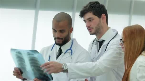 Drei selbstbewusste Ärzte untersuchen Röntgenbild der Lungen