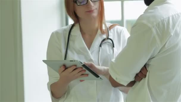 Doctor shows the patient survey results on the tablet