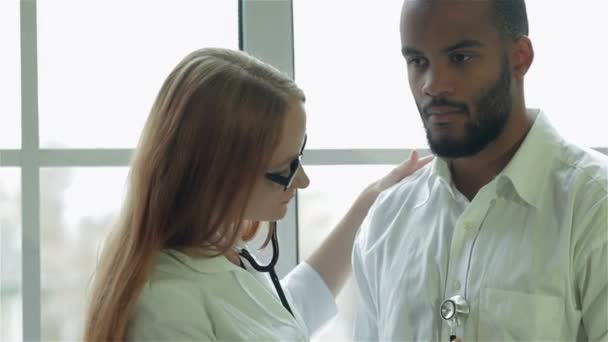 The doctor examines the patient with a stethoscope