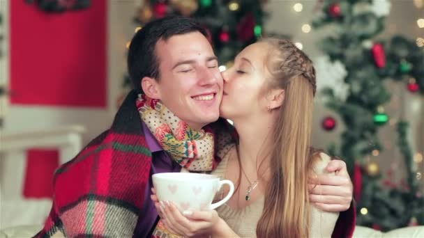 Young beautiful couple holding hands with a cup of cocoa