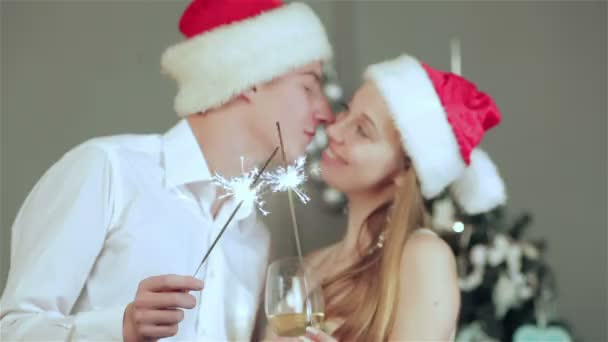 Beautiful couple in Santa hat holding sparklers in hand and kiss