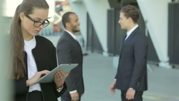 Business woman standing in the street while two businessmen shaking hands