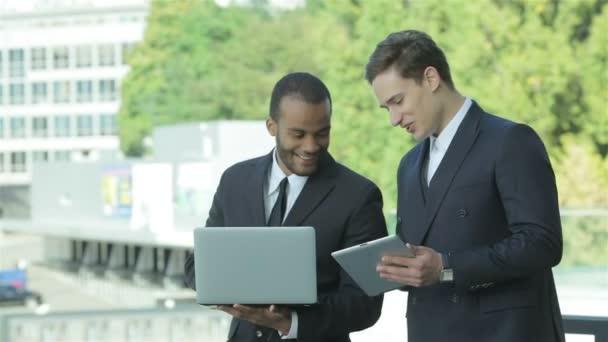Dva sebejistí obchodník s tabletem a laptopem