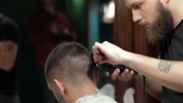 Young stylish tattooed barber cutting hair of a young man at barbershop
