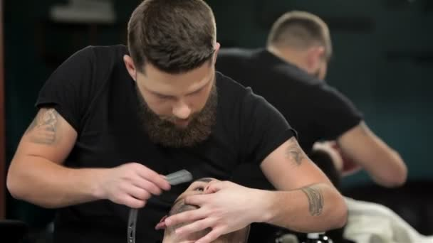 Young man getting an old-fashioned shave with straight razor