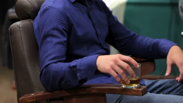 A man with a whiskey in the barbershop