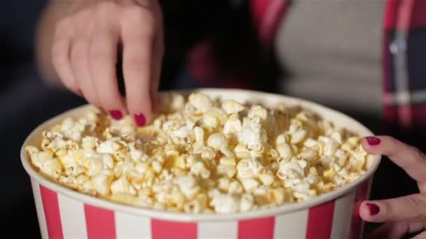 Nahaufnahme Eimer Popcorn und eine Hand des Mädchens