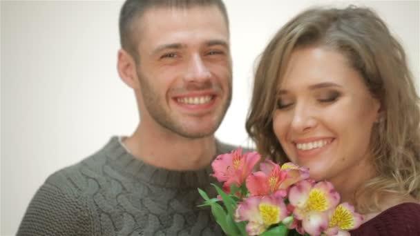 Pár v objetí drží kytici květin