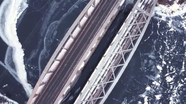 sanfter Flug mit einer Drohne über eine Brücke und einen zugefrorenen Fluss, Autos passieren die Straße, Winterzeit, kalte Töne, sanfter Höhenflug mit einer Drehung