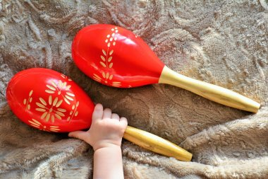 Couple of red wooden maracas and baby hand