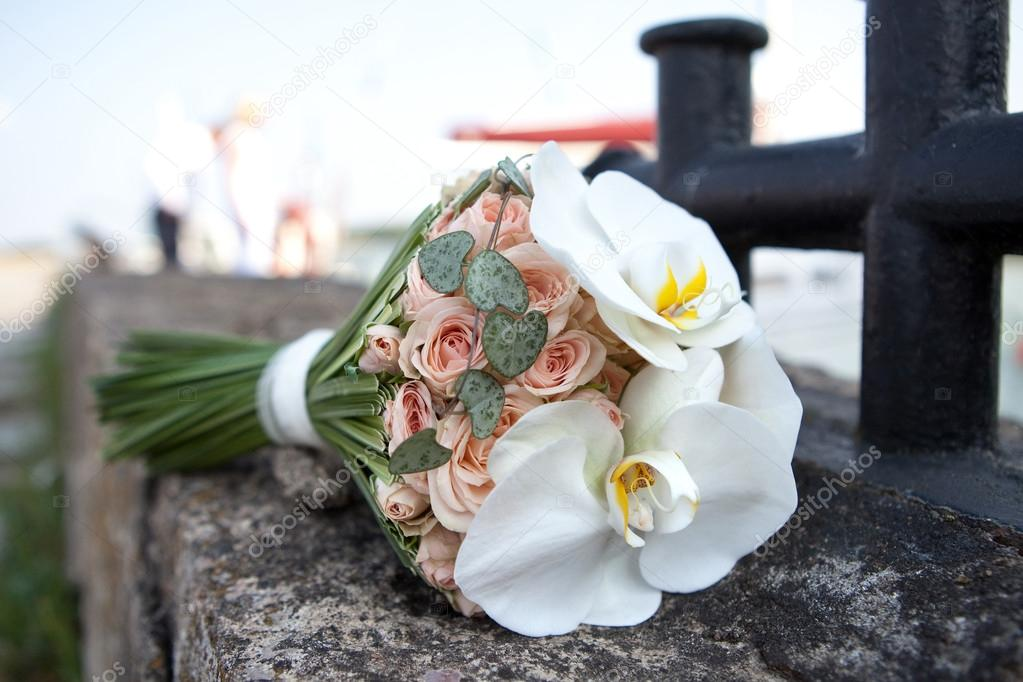 Bouquet of fresh flowers near the bollard. Wedding bouquet of roses and orchids.