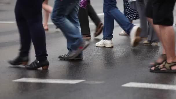 Přechod pro chodce. Lidé v různých boty přes ulici. Život ve městě