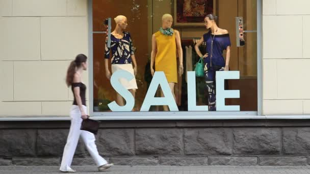 Sale. Woman passing by shop window and looking at mannequins.