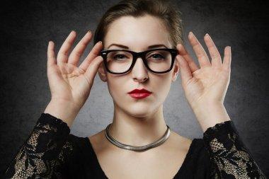 Beautiful seducing femme fatale in nerdy glasses