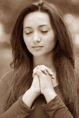 Woman praying outdoors
