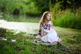 Girl in the Ukrainian national clothes with wreaths of flowers o