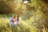 two girls in Ukrainian national dress sitting on the grass. Girl