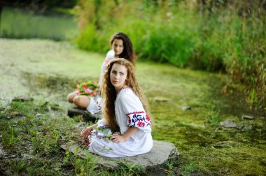 Two girls in the Ukrainian national clothes with wreaths of flow