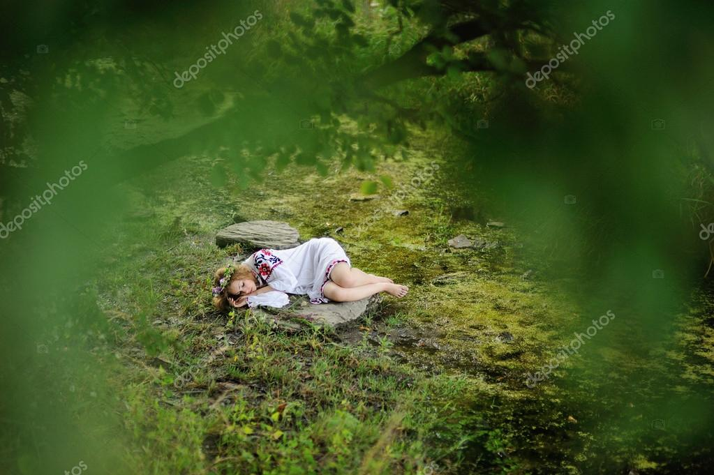 Ukrainian girl in shirt and wreath on his head sleeping on a roc