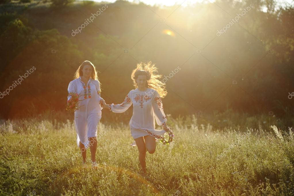 two girls in the national Ukrainian clothes with wreaths of flow