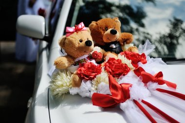 Two toy bear on the hood of wedding car. Toy bears dressed in Co