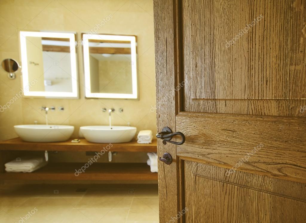 badkamer voor een open houten deur twee putten voor badkamers en tw stockfoto