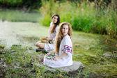 Két lány ukrán ing van a háttérben, a folyó