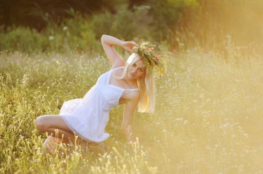Ukrainian girl in a white sundress with a wreath of flowers on h