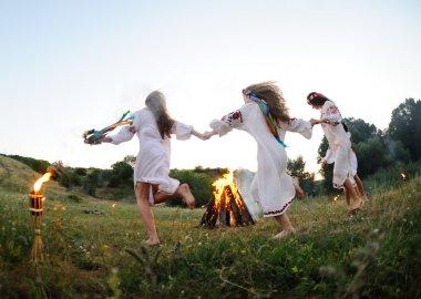 Girls in Ukrainian national shirts dancing around a campfire