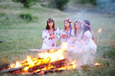Ukrainian girl in shirts sitting around the campfire