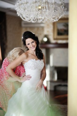 Mom helps the bride to wear a wedding dress. morning bride