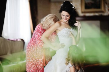 mom and little girl help the bride to wear a wedding dress. morn