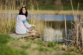 Fotografie Slavic girl in Ukrainian shirt sitting on the bridge with Easter