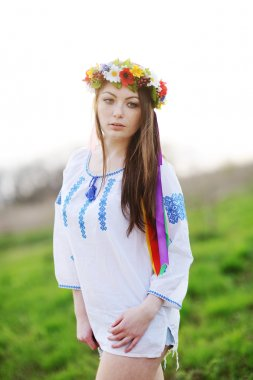 Ukrainian girl in a shirt and a wreath of flowers and ribbons on