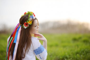 Ukrainian girl in a shirt and a flower wreath on his head on a b
