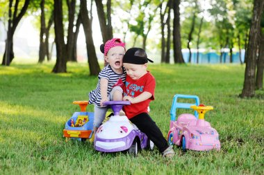 little boy and girl quarrel over a toy car