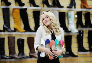 Beautiful girl chooses shoes. blonde girl measures the boots in the store
