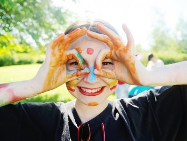 Cheerful young girl with bright colors smeared face.