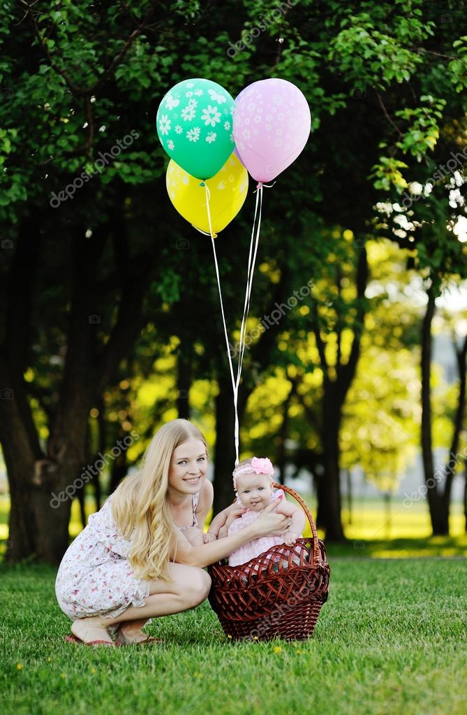 Daughter with her mother relaxing in the park on the grass. little girl in the basket with balloons
