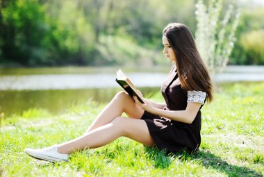 Schoolgirl with a book relaxing in the park on the grass