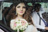 Fotografie Portrait eines Mädchens hinter nassen Glas. Die Braut in einem Hochzeitsauto
