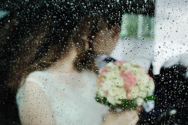 the bride and groom for a wet glass wedding car