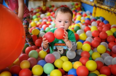 baby boy looking with surprise at the colored balls. child squin