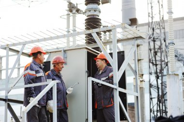 workers repairing a transformer at the power station.