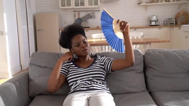 Schwarze Frau mit Hitzschlag in Wohnung ohne Klimaanlage und Ventilator zu Hause auf Couch liegend