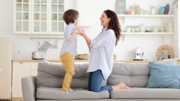 Matka a dítě se smáli, bavili se, drželi se za ruce a skákali doma na pohovce. Šťastná rodina.
